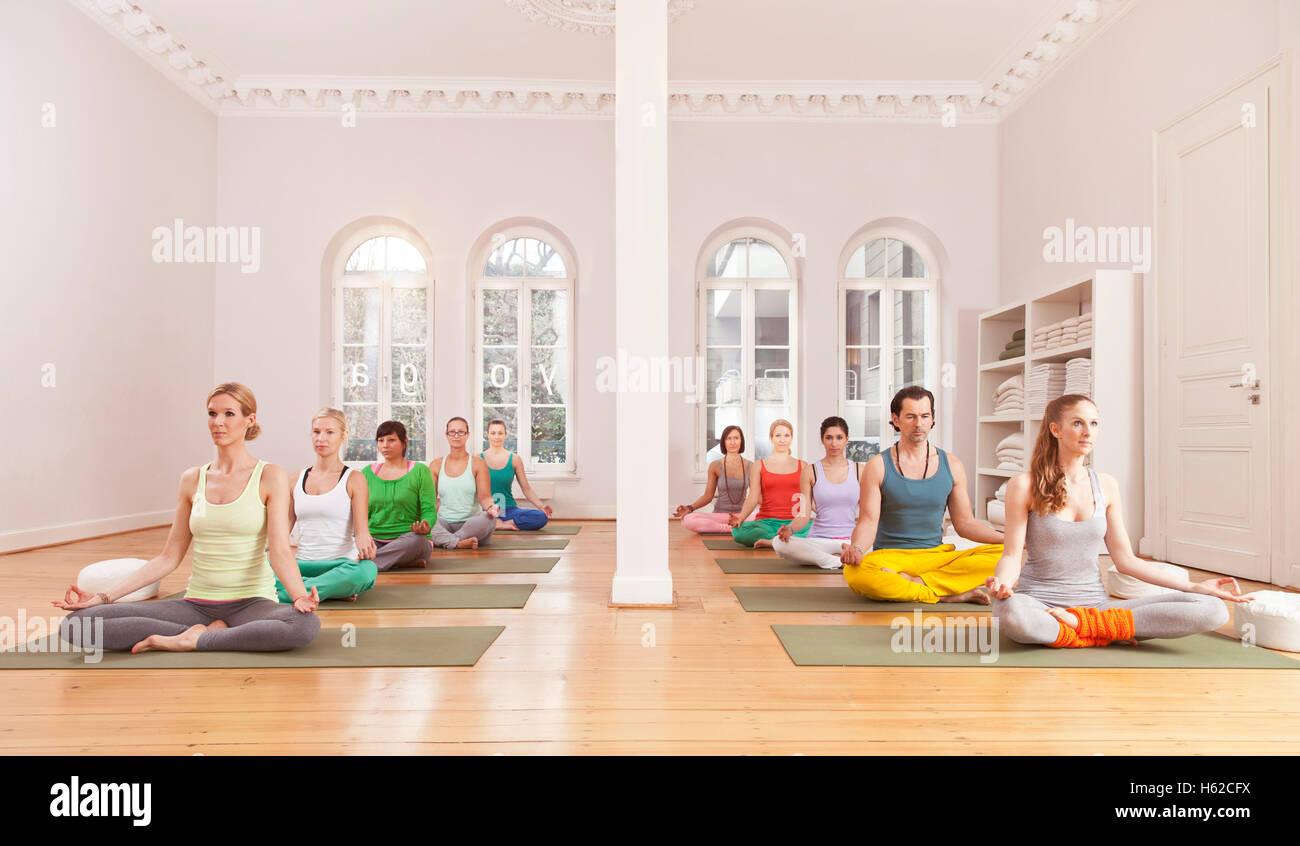 Group of people in yoga studio sitting in Lotus pose - Stock Image