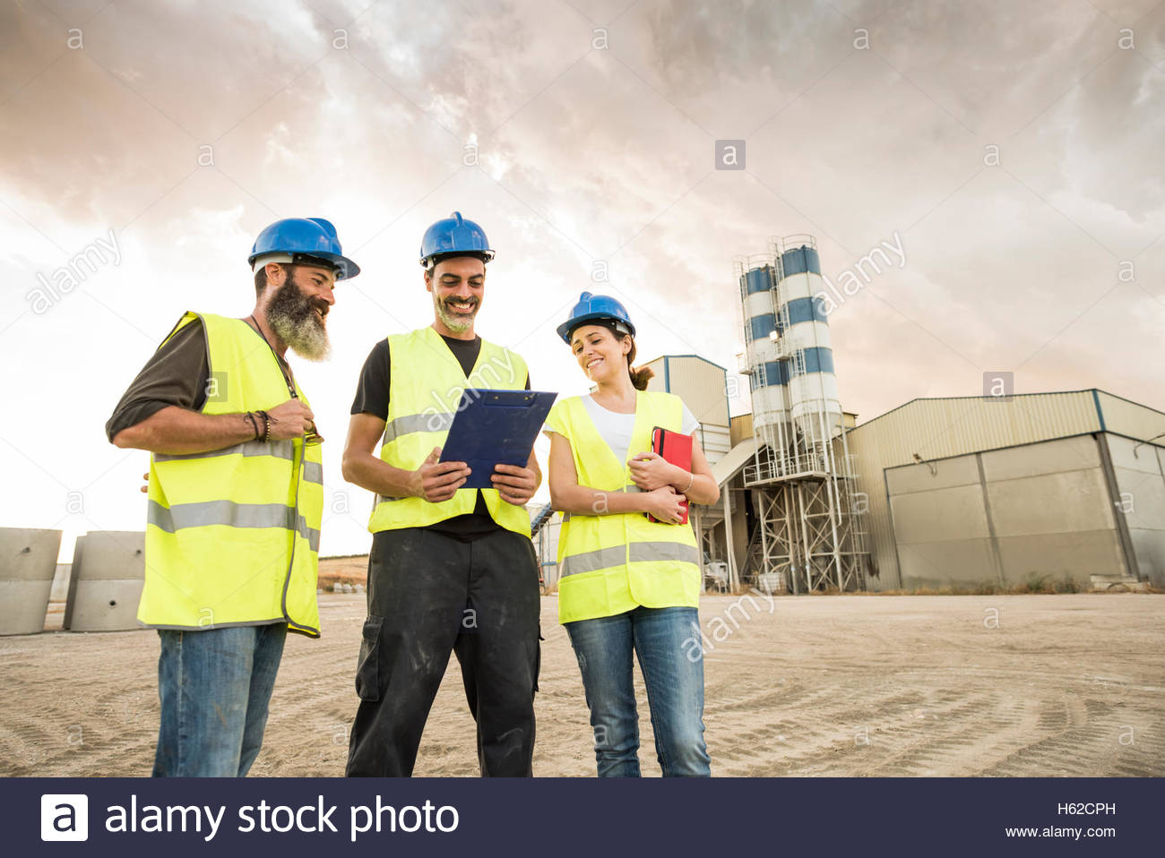 Three people in safety vests on industrial site - Stock Image