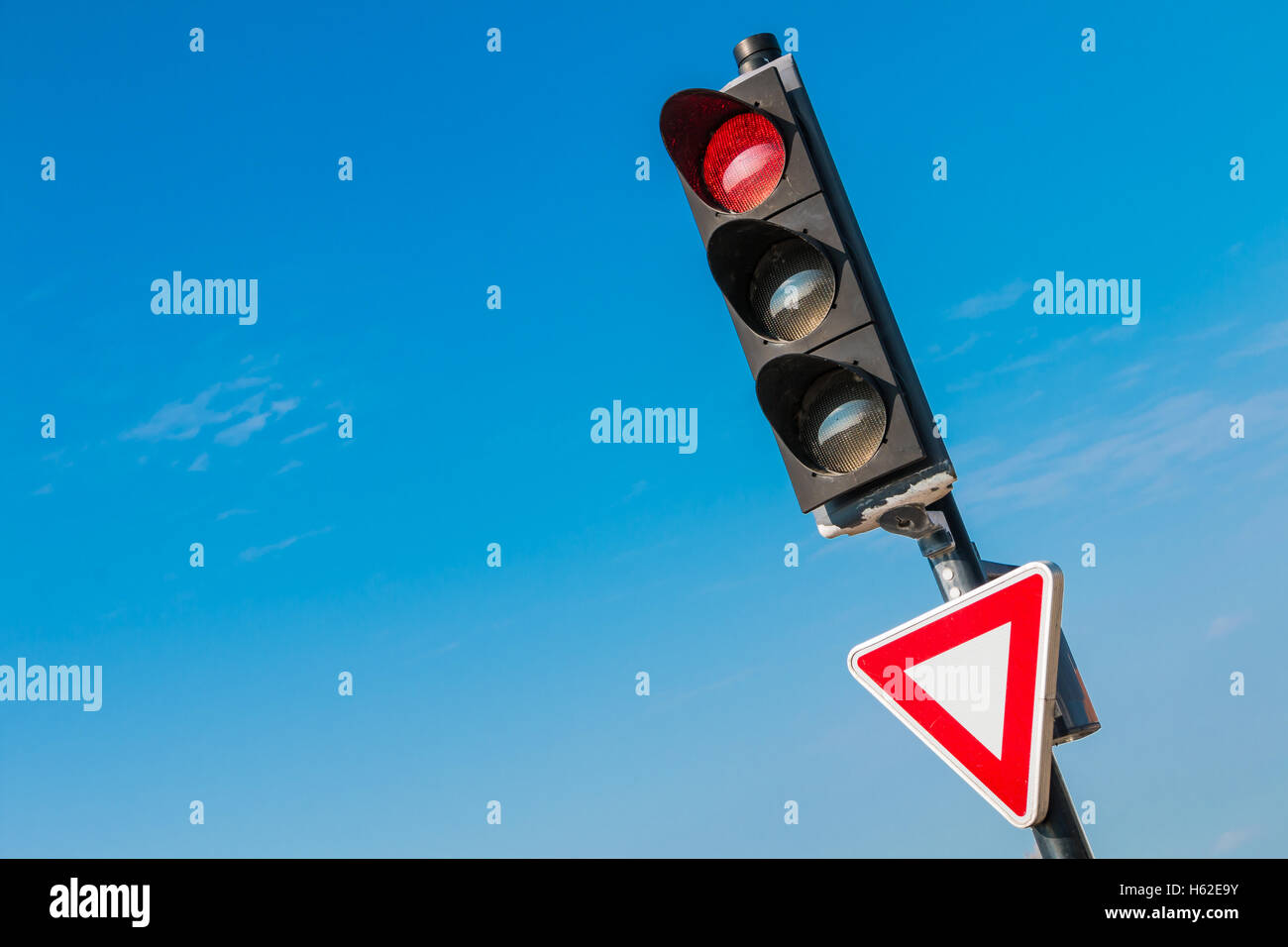 red traffic light with yield sign on blue sky - Stock Image