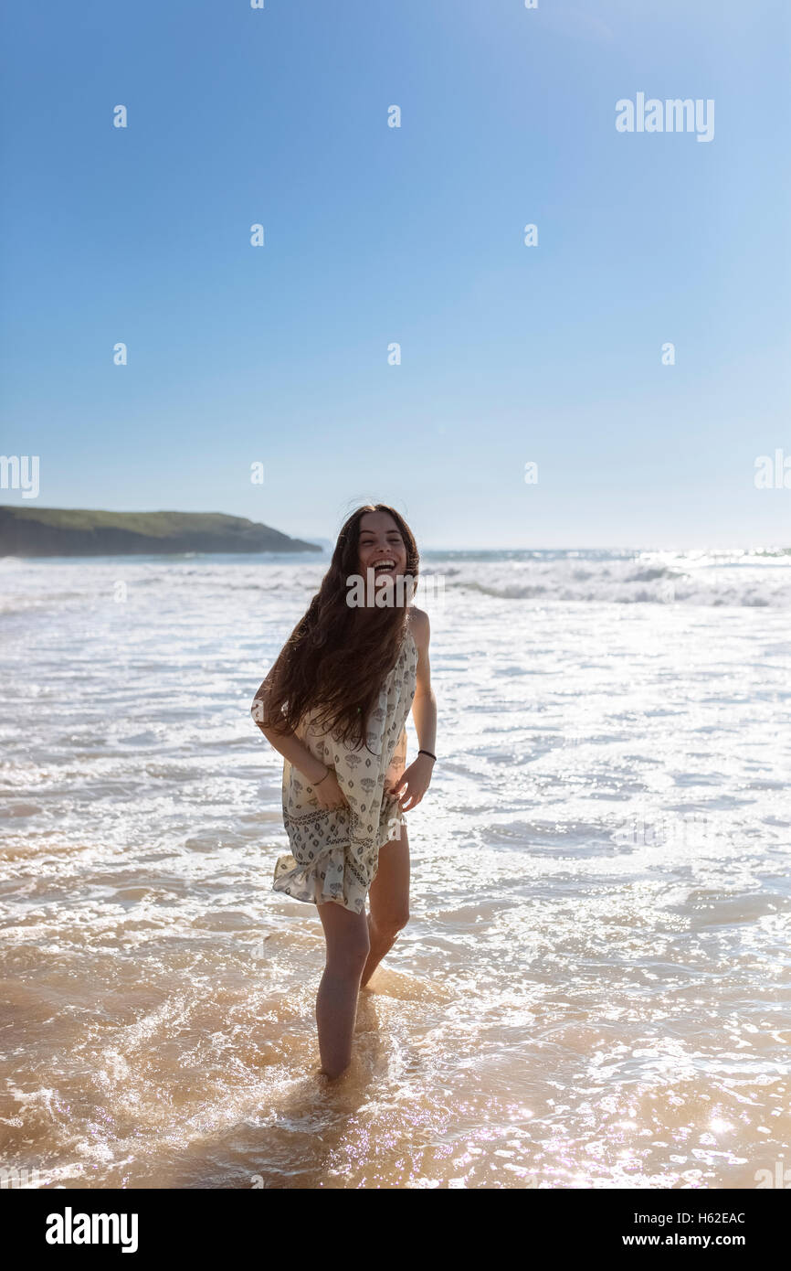 Laughing young woman standing in the water at seaside - Stock Image