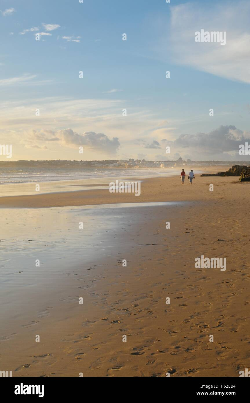 Distant figures walking on beach in the golden evening light Stock Photo