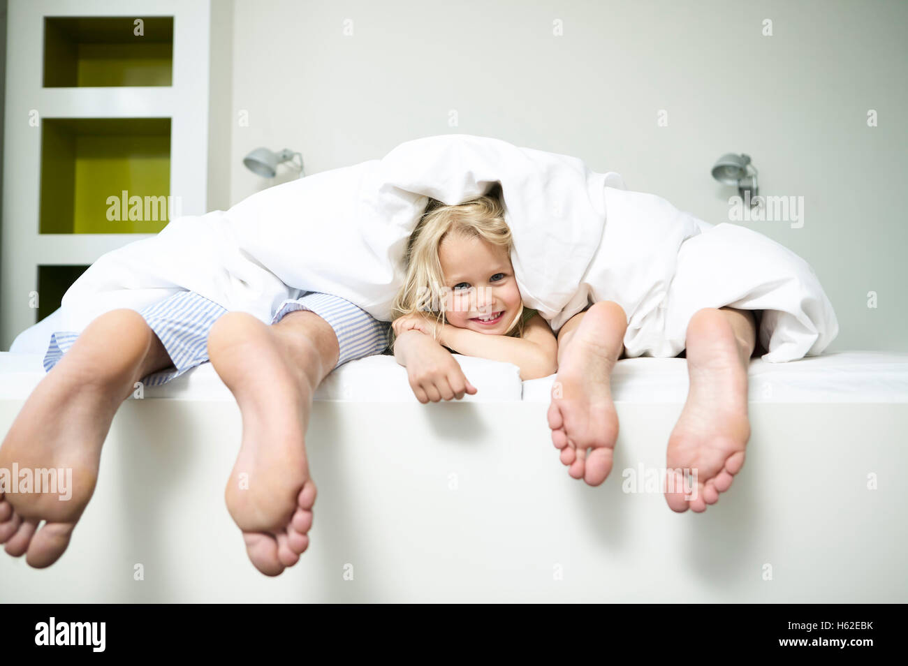 Family lying in bed of hotel room, daughter looking from between parents feet - Stock Image