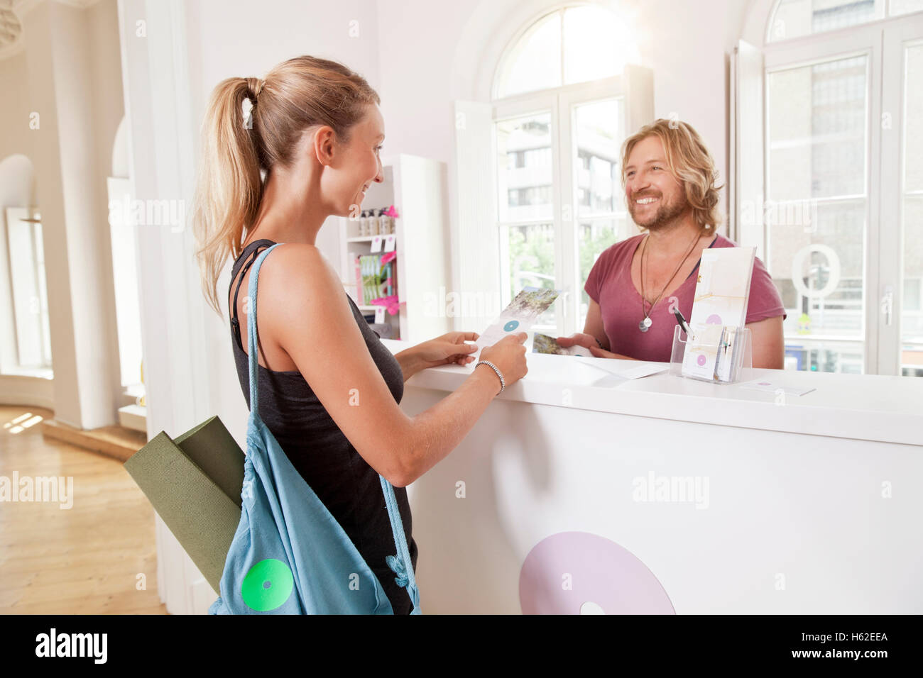 Woman at yoga studio counter informing about classes - Stock Image