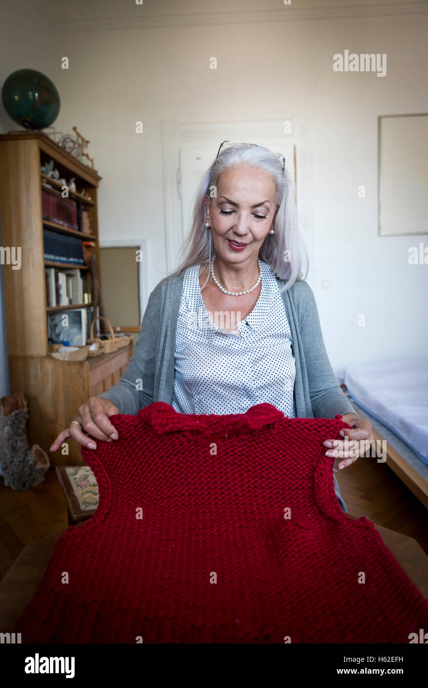 Content woman looking at knitted sweater vest - Stock Image