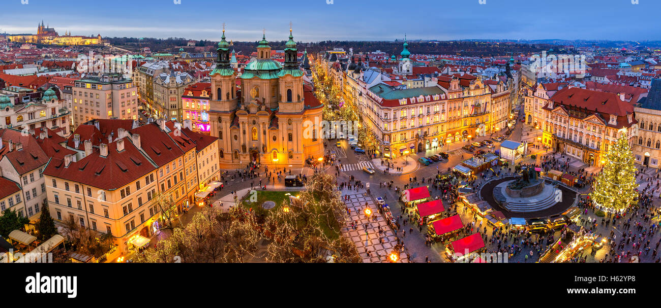 Panoramic view from above of city skyline, illuminated buildings and traditional Christmas market in Prague. - Stock Image