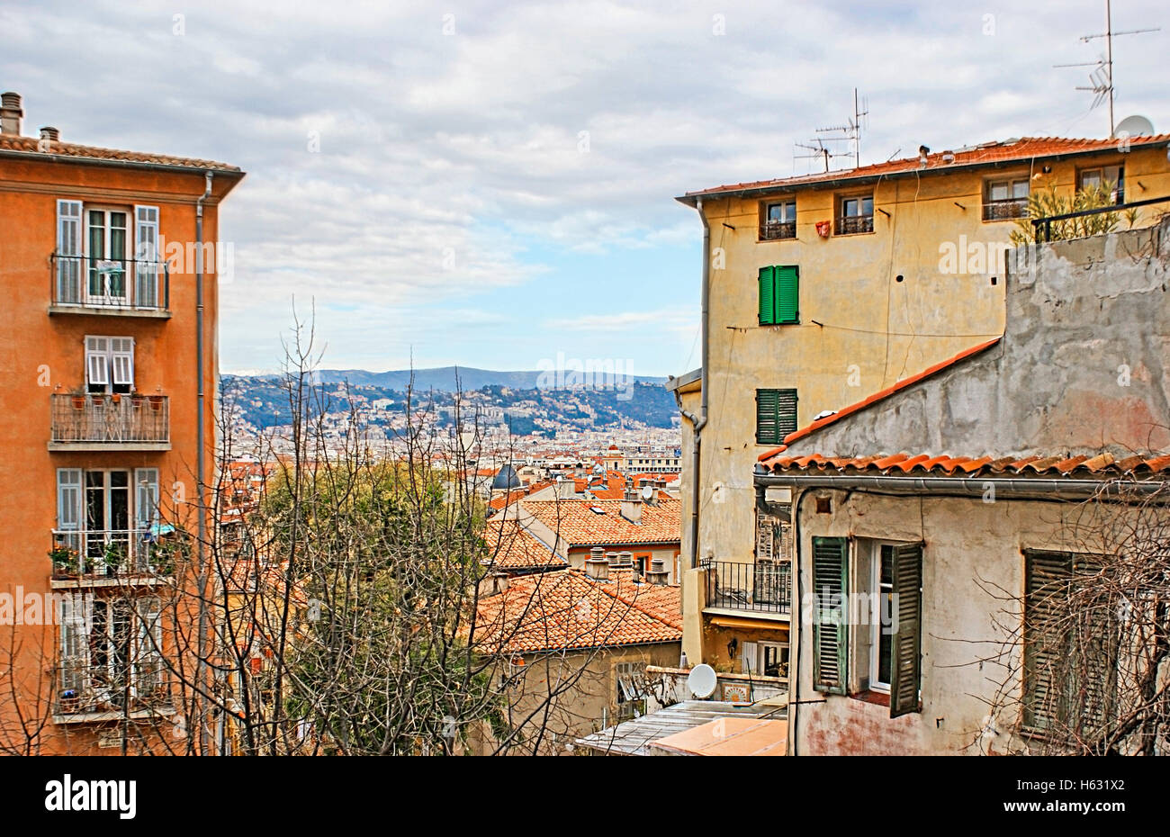 The reward for those who went up the city hill is the view on the tiled roofs and the mountains of Cote d'Azur - Stock Image