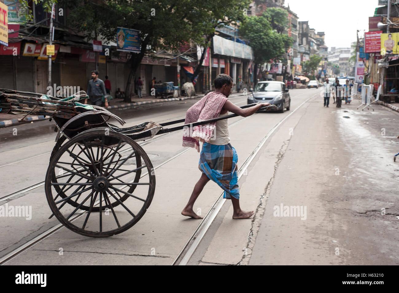 A Hand Pulled Rickshaw passing  on  Tram line street kolkata west Bengal India Stock Photo