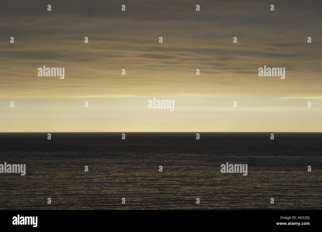 An arty / moody shot of the horizon, with a thick straight line of sandy looking cloud close to the sea. Aberystwyth. - Stock Image