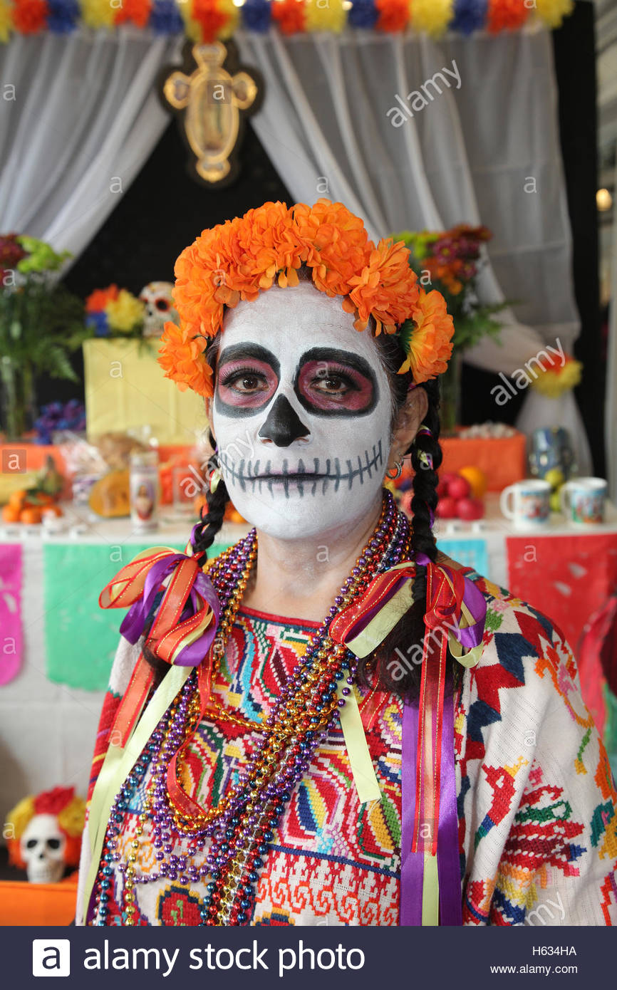 Mexican woman wearing skeleton make-up stands by offerings for her deceased loved ones during the Day of the Dead - Stock Image