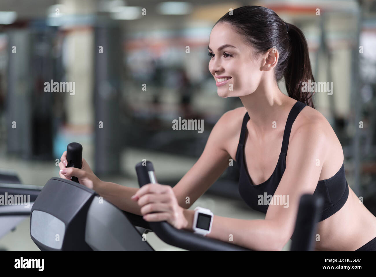 Smiling woman running on a treadmill - Stock Image