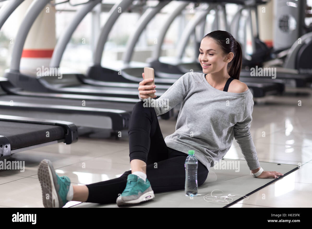 Beautiful girl using smartphone in a gym - Stock Image