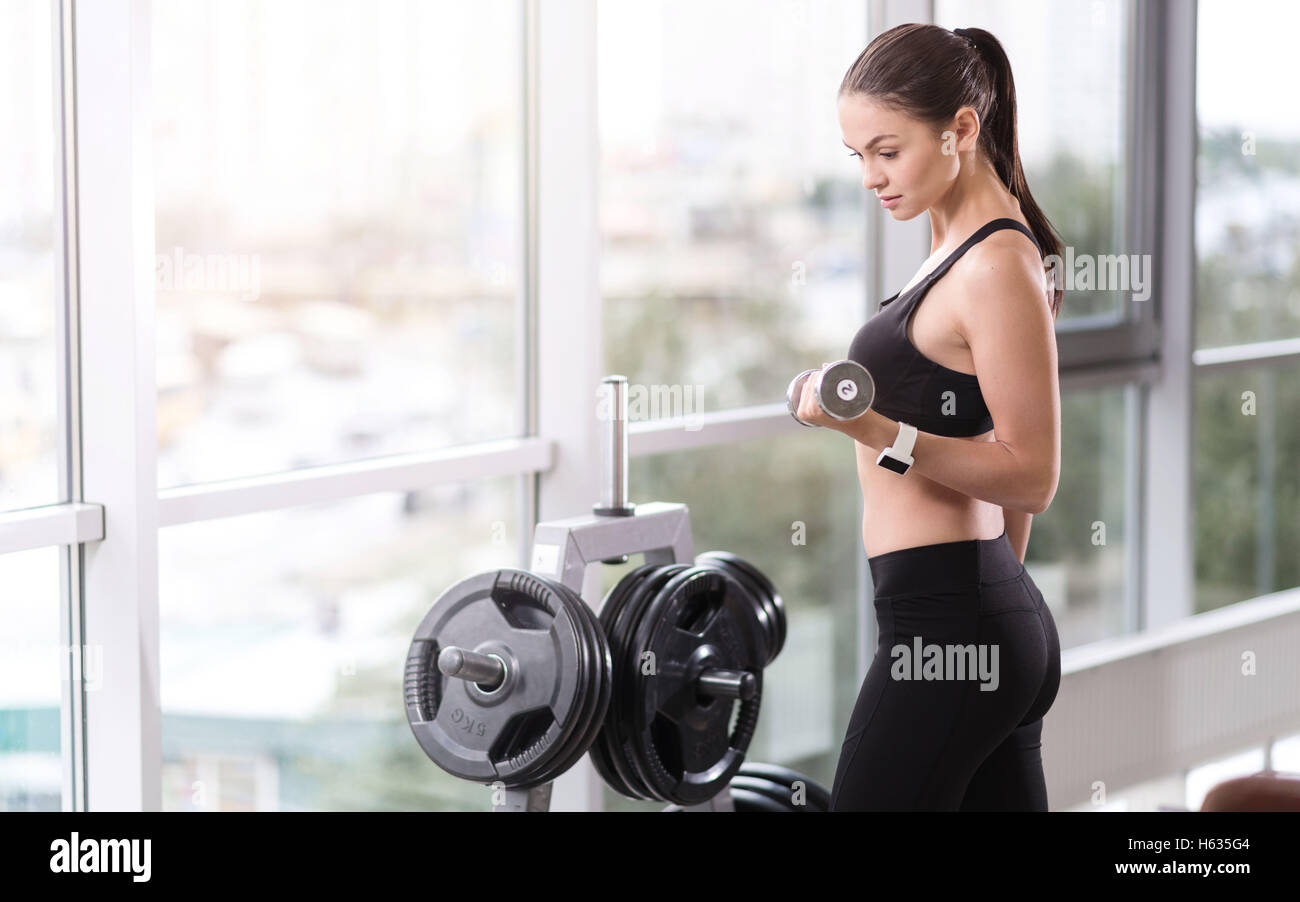 Strong girl using dumbbells in a gym - Stock Image