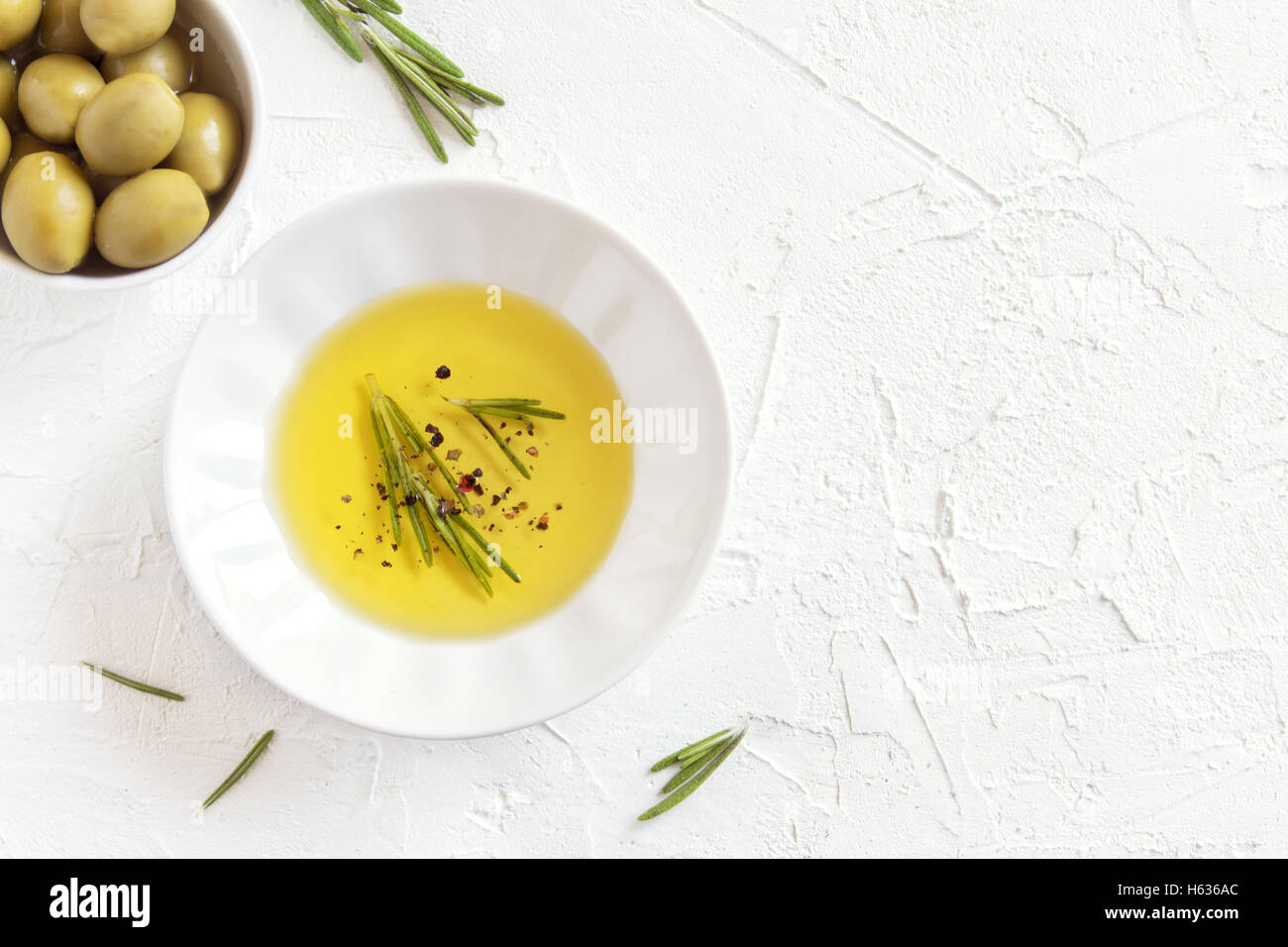 Organic olive oil with rosemary and spices (peppers) over white stone background with copy space, healthy food concept - Stock Image