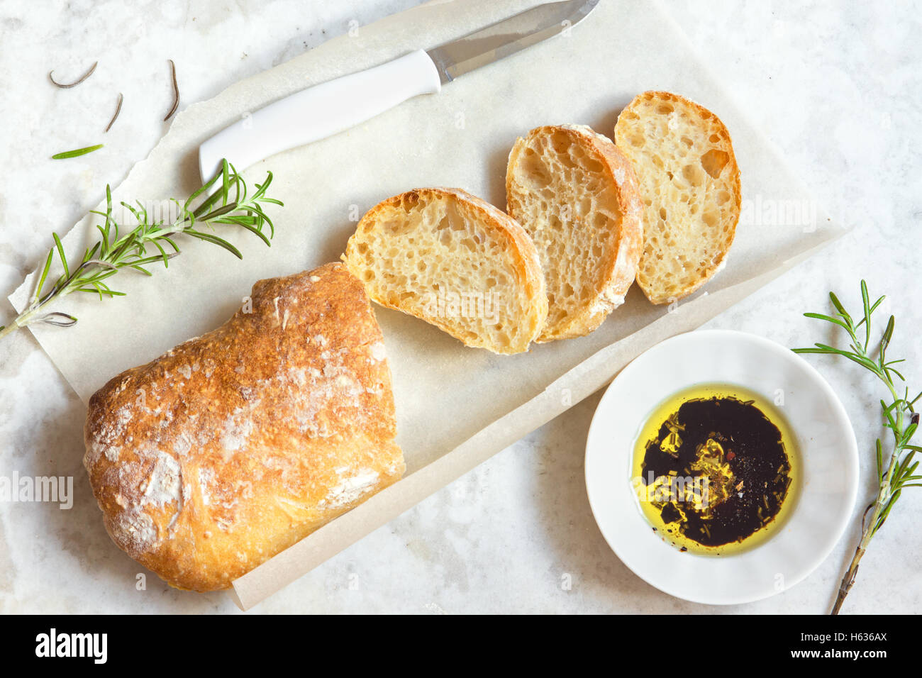 Italian bread Ciabatta with olive oil and rosemary on white marble background - fresh homemade bread bakery - Stock Image