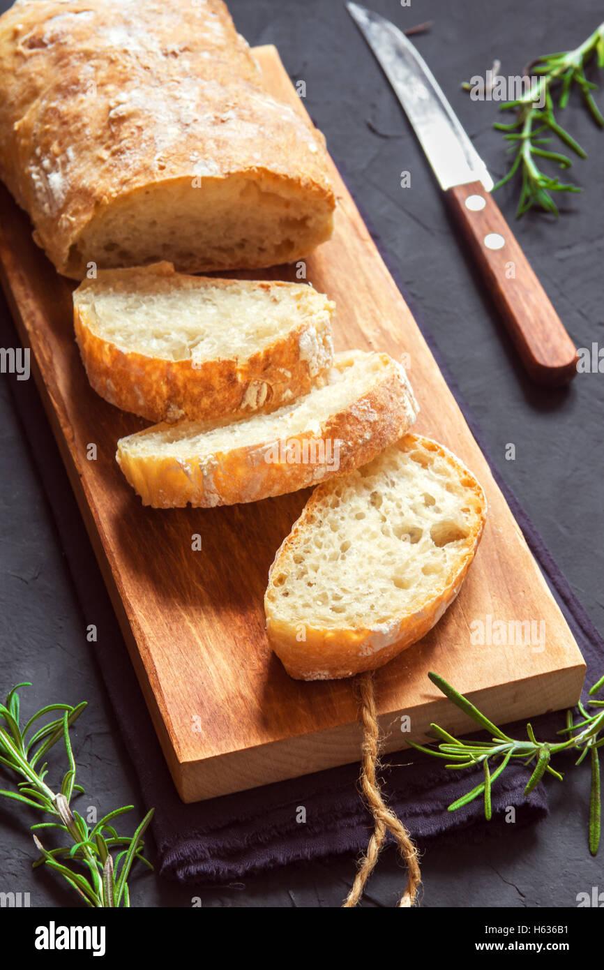 Italian bread Ciabatta and rosemary on black background - fresh homemade bread bakery Stock Photo