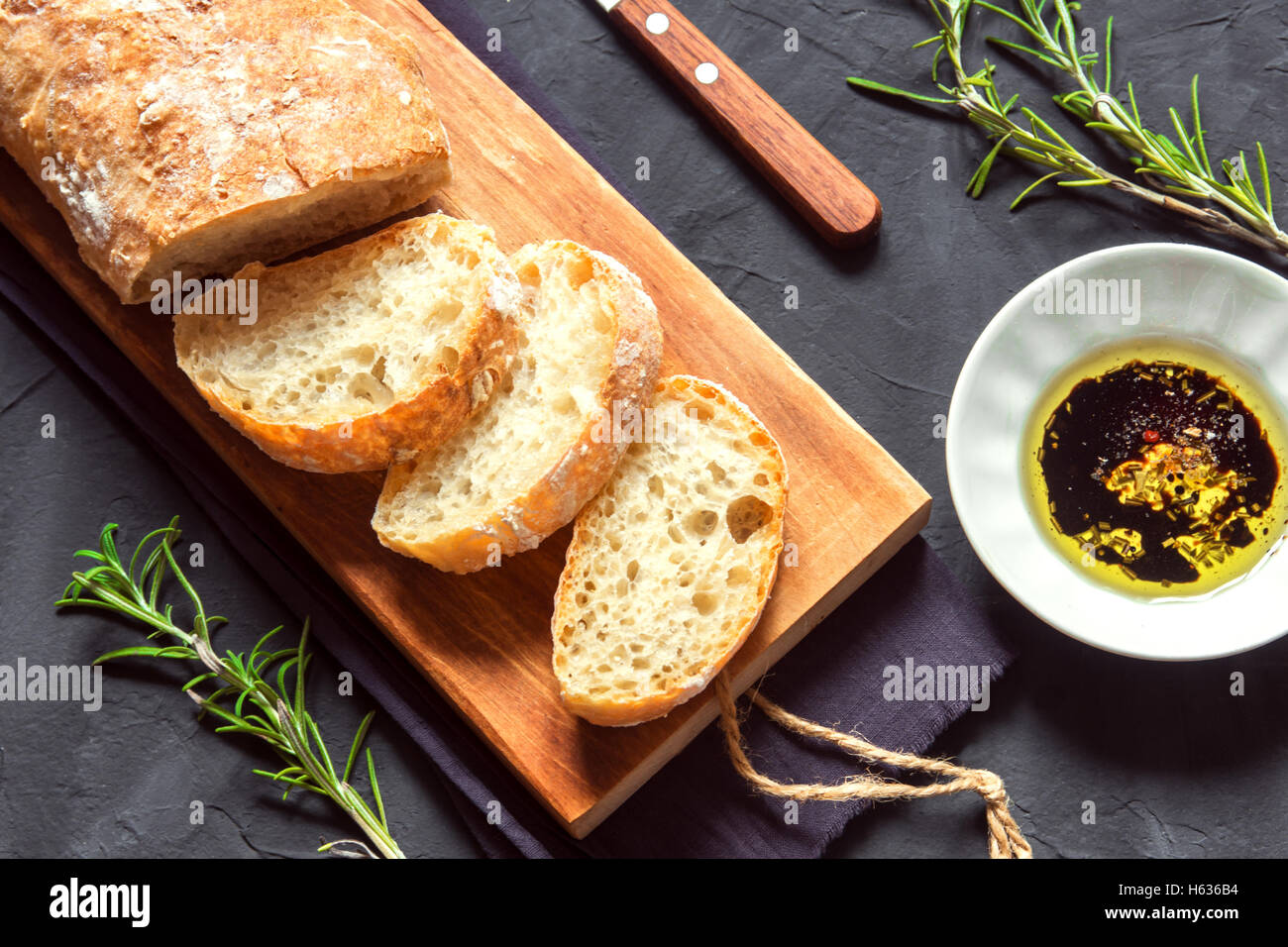 Italian bread Ciabatta with olive oil and rosemary on black background - fresh homemade bread bakery - Stock Image
