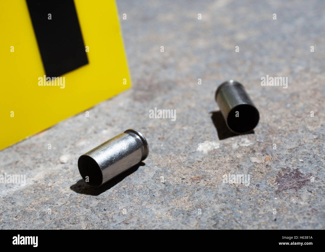 Pair of handgun casings that are on concrete with an evidence marker - Stock Image