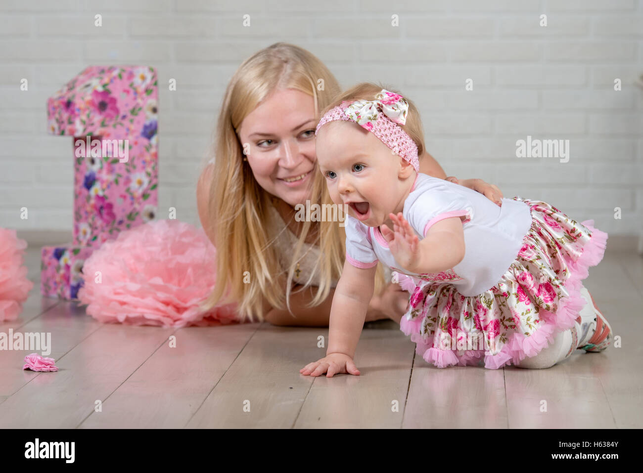 Happy one year old girl with her young and beautiful mother Stock Photo