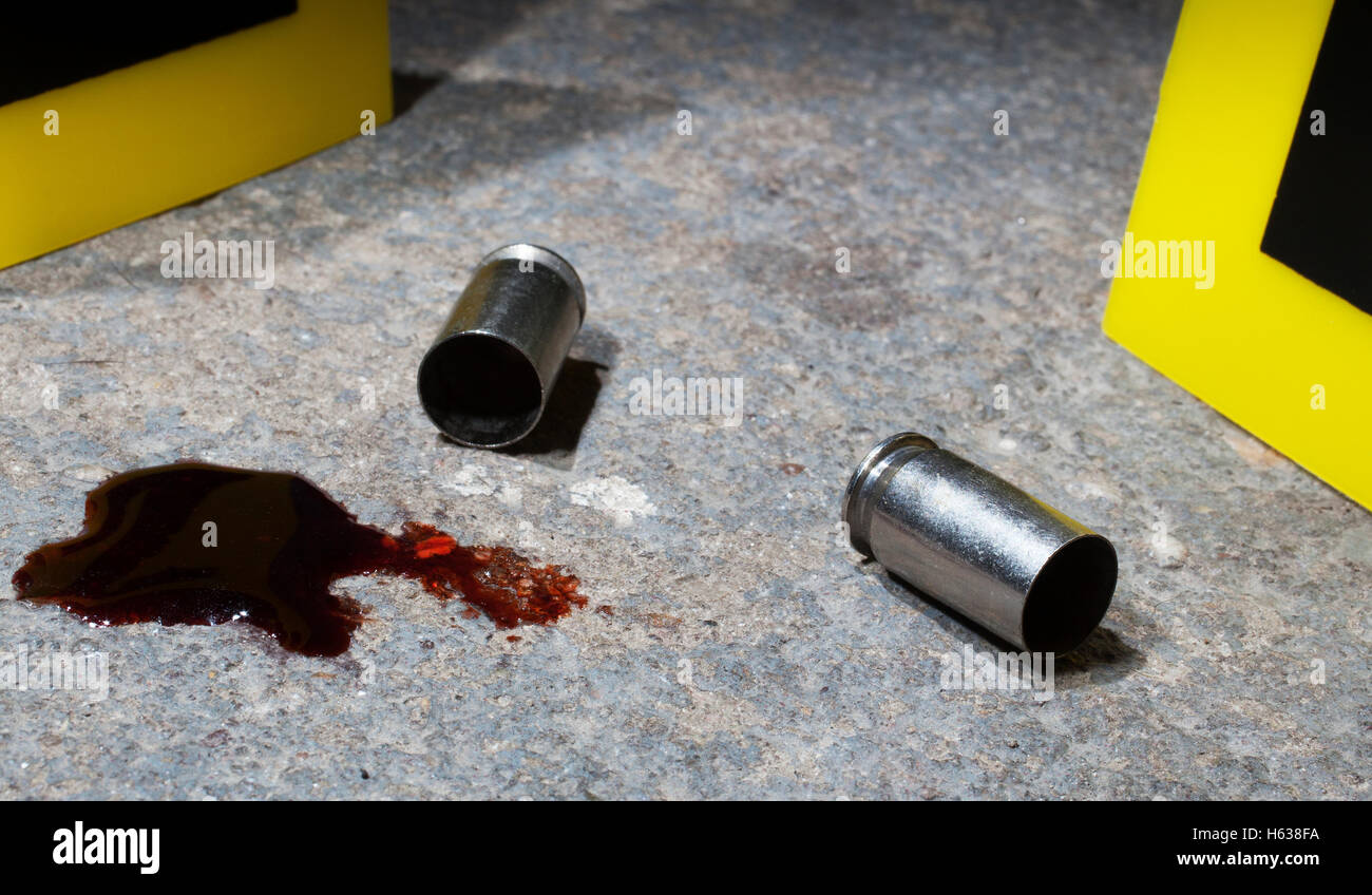 Blood and empty handgun ammo with evidence markers on concrete - Stock Image