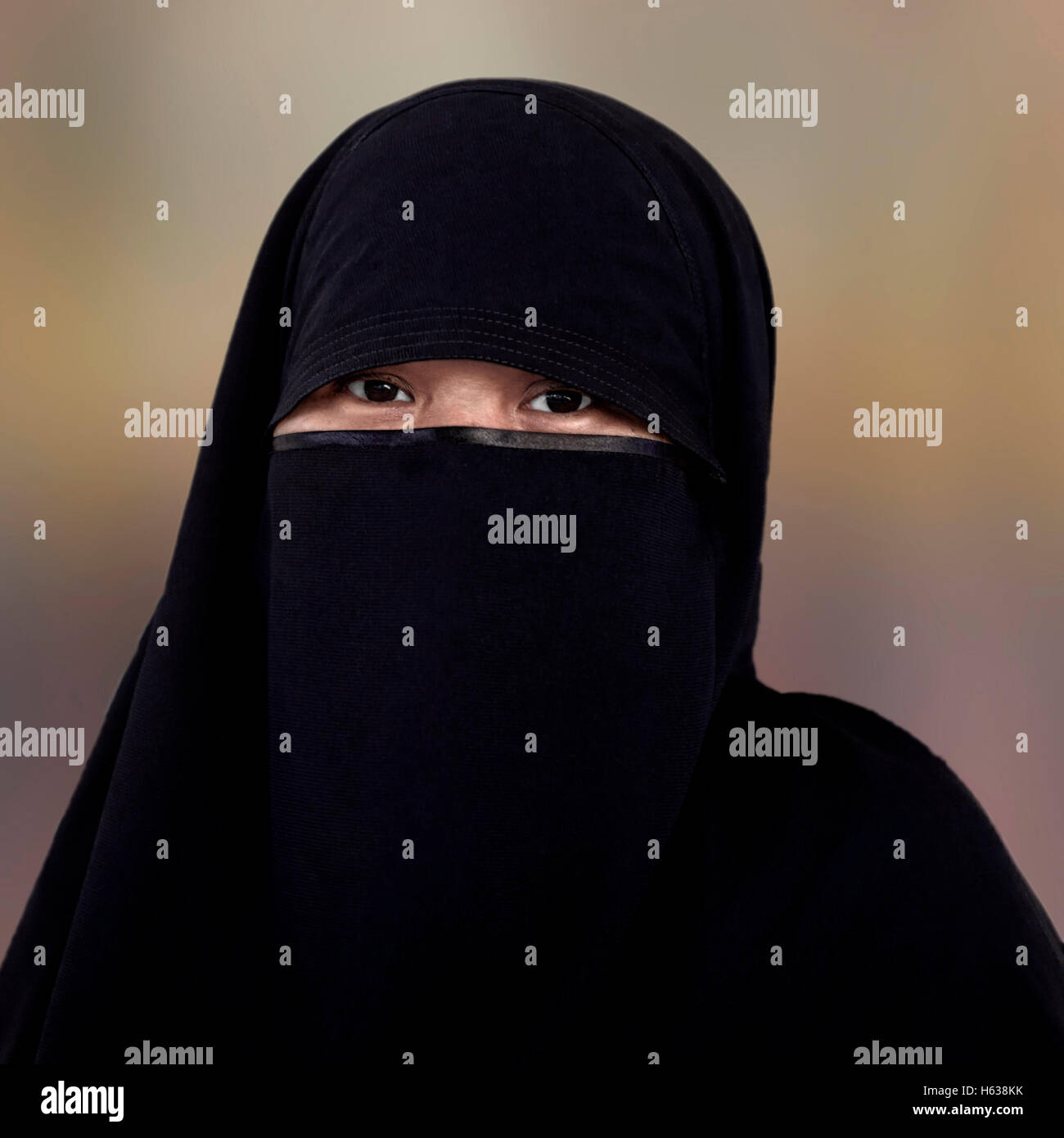Muslim woman niqab burka isolated against a plain background. Woman eyes hijab - Stock Image