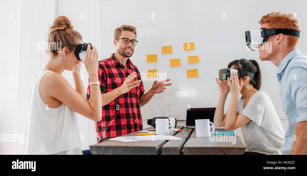 Business people using virtual reality goggles during meeting. Team of developers testing virtual reality headset - Stock Image