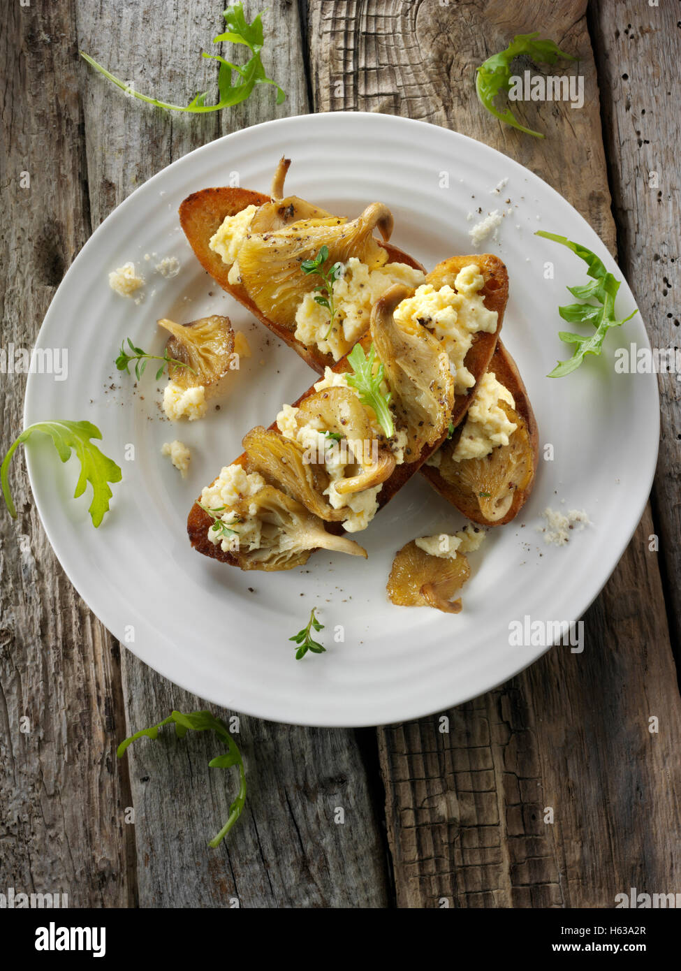 Yellow Oyster mushrooms sauteed in butter and served with scambled egg on sour dough toast with wild rocket - Stock Image