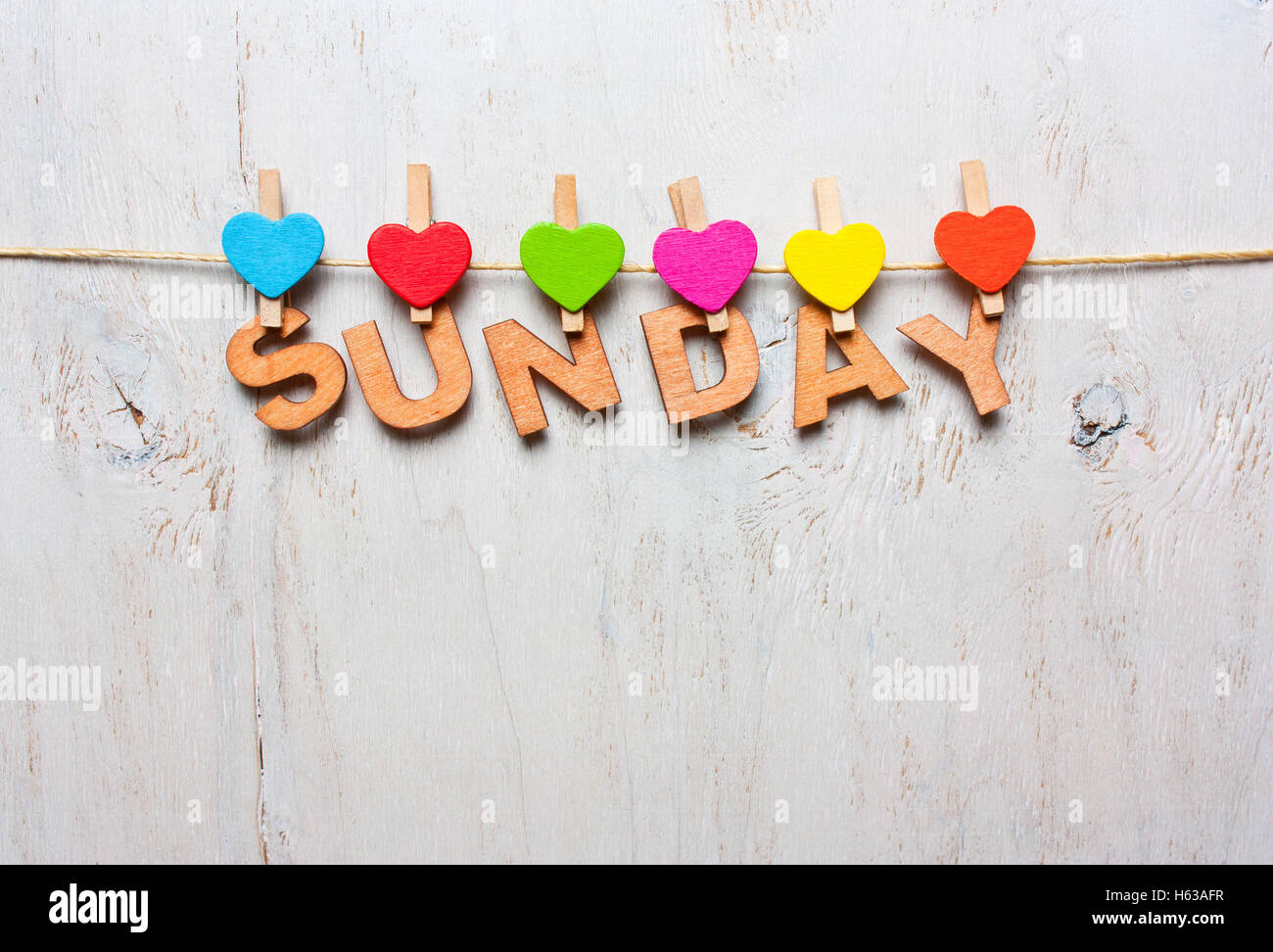 sunday word from wooden letters with colored clothespins on a white wooden background