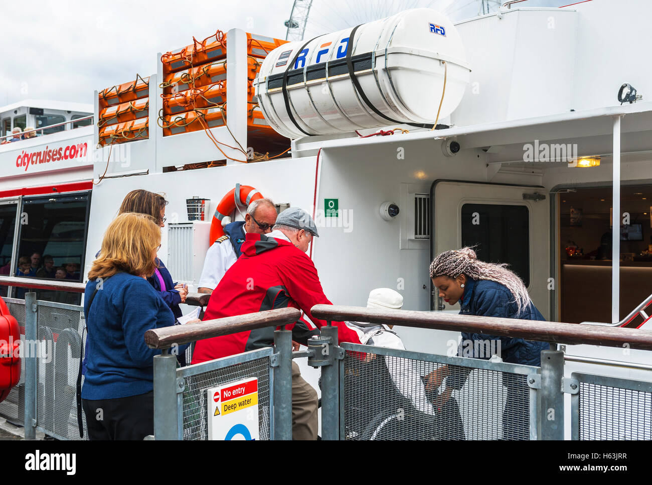 London, the UK-May 2016: helping a disable person to embark for the Thames cruise - Stock Image