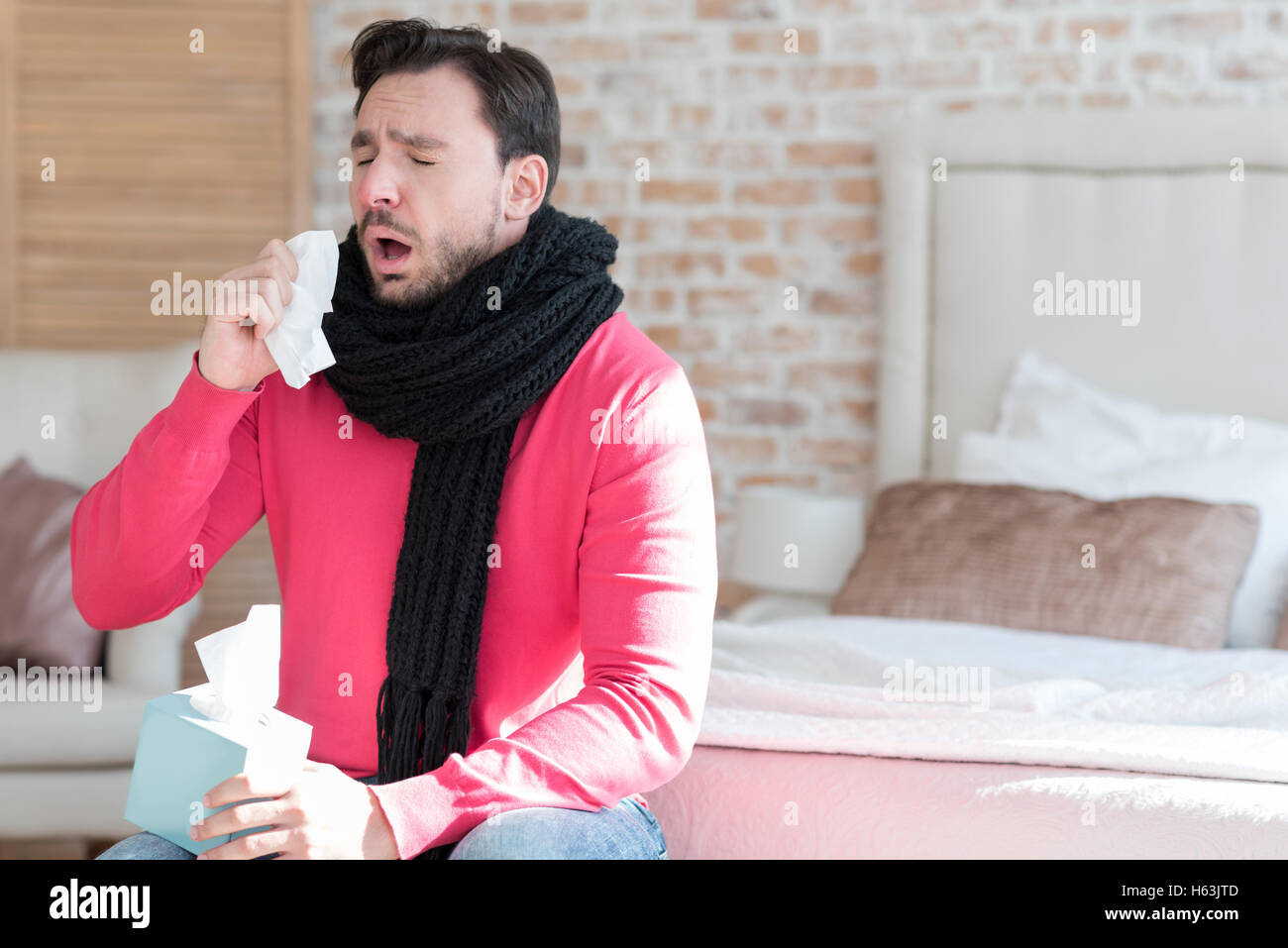 Ill young man sneezing - Stock Image