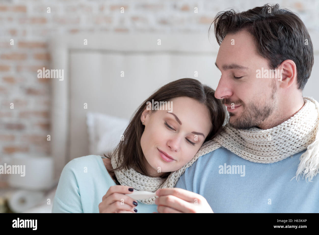 Cheerful optimistic couple looking at the body thermometer - Stock Image