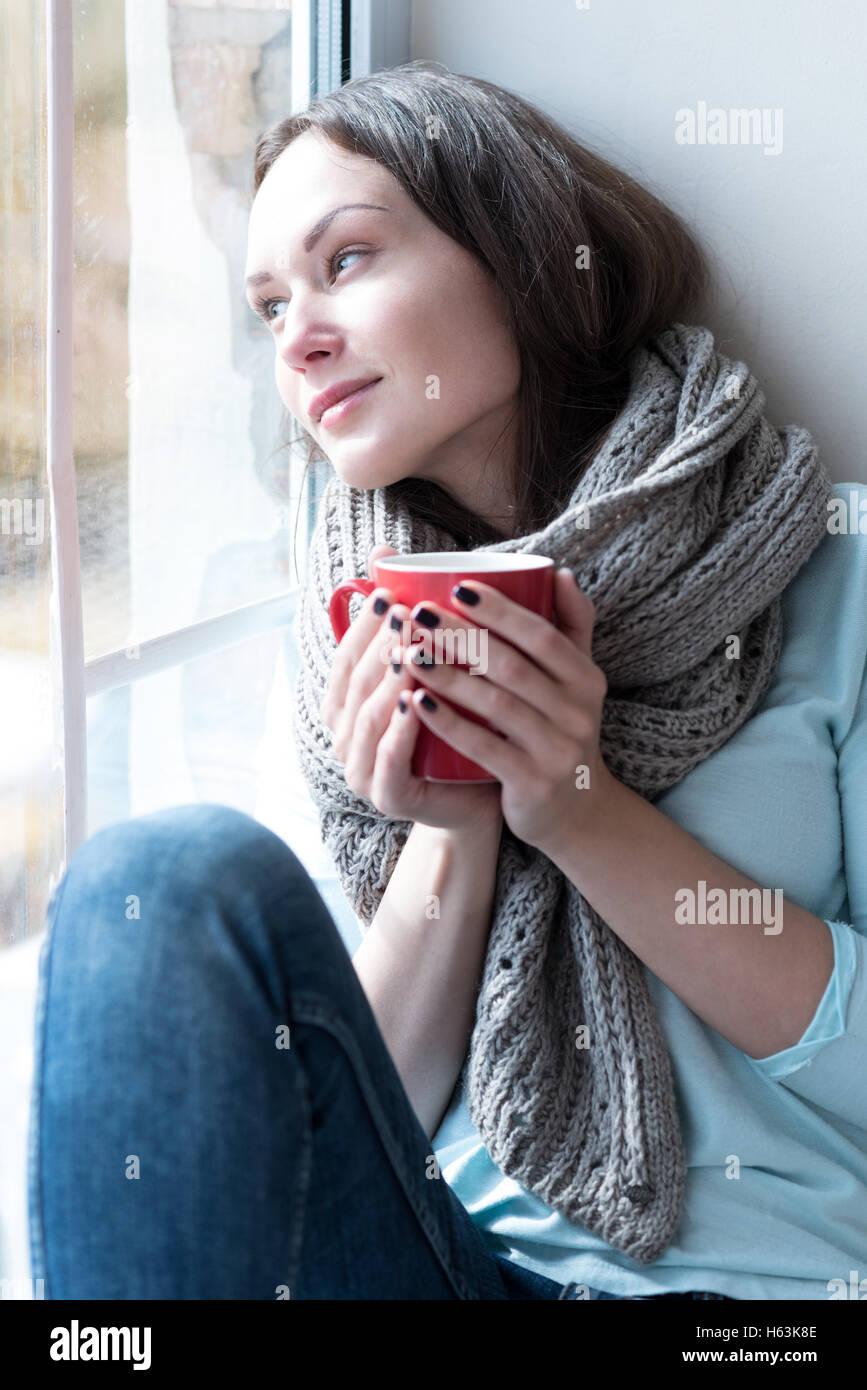 Calm dreamy woman leaning on the window glass - Stock Image