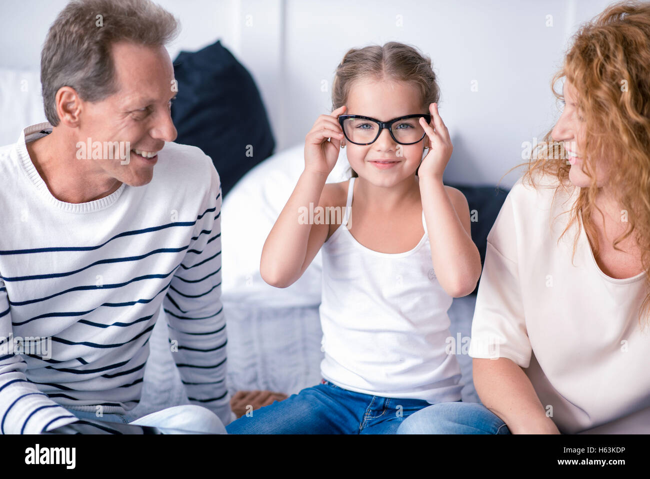 Little girl wearing glasses and smiling with her grandparents - Stock Image