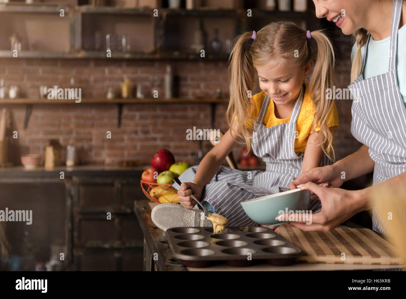 Smiling involved girl helping her mother cooking pastry - Stock Image
