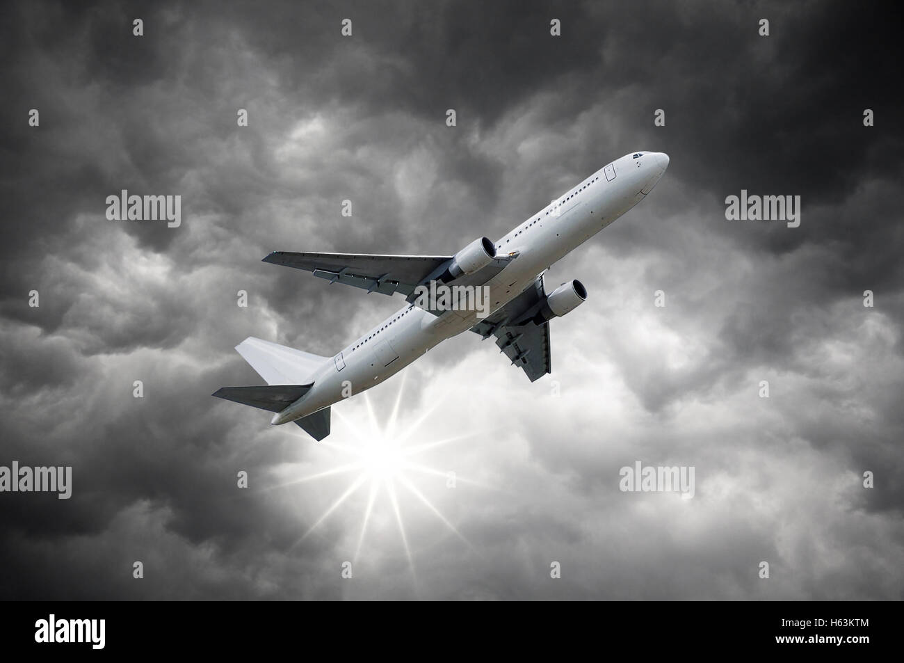 Airplane above the Sun shining from dark clouds of storm sky - Stock Image