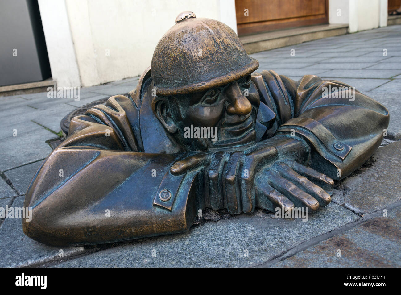 A bronze statue representing a street worker emerging from a manhole. On a street in the city centre of Bratislava, - Stock Image
