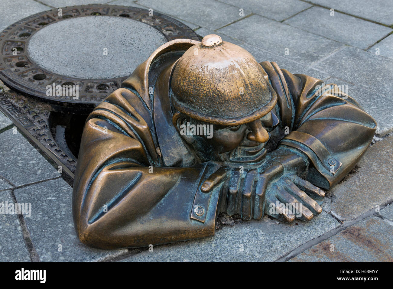 A bronze statue representing a street worker emerging from a manhole. Bratislava, Slovakia. - Stock Image