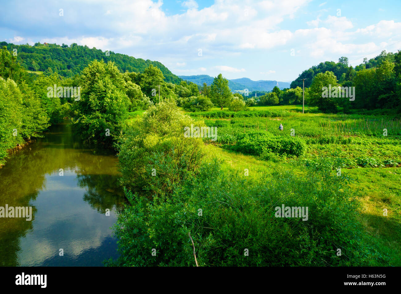 View and countryside, with a farmer, along the M18 road in the Republika Srpska, Bosnia and Herzegovina - Stock Image