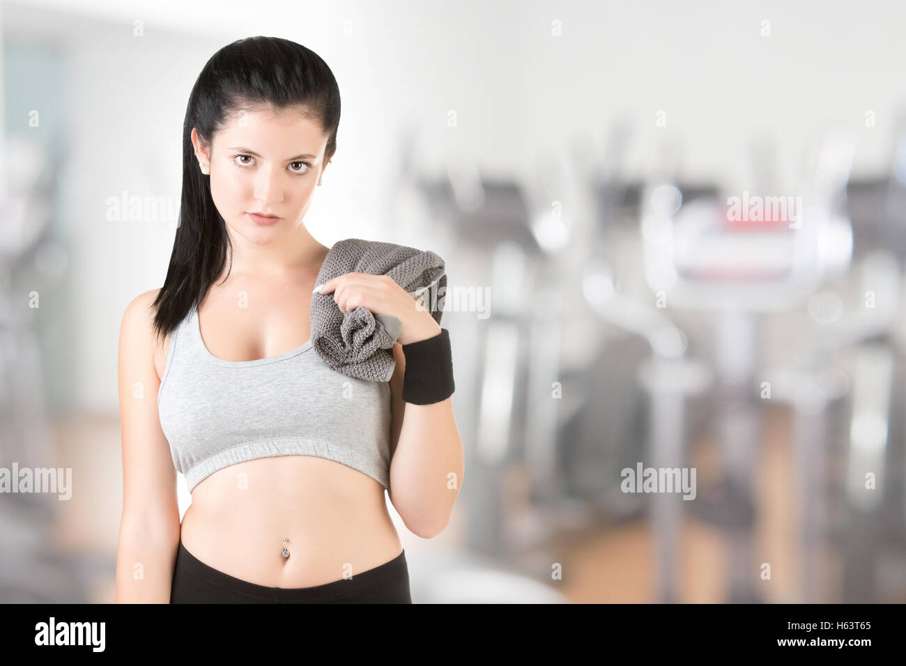 Woman resting with a towel around her neck after a fitness workout, in a gym - Stock Image