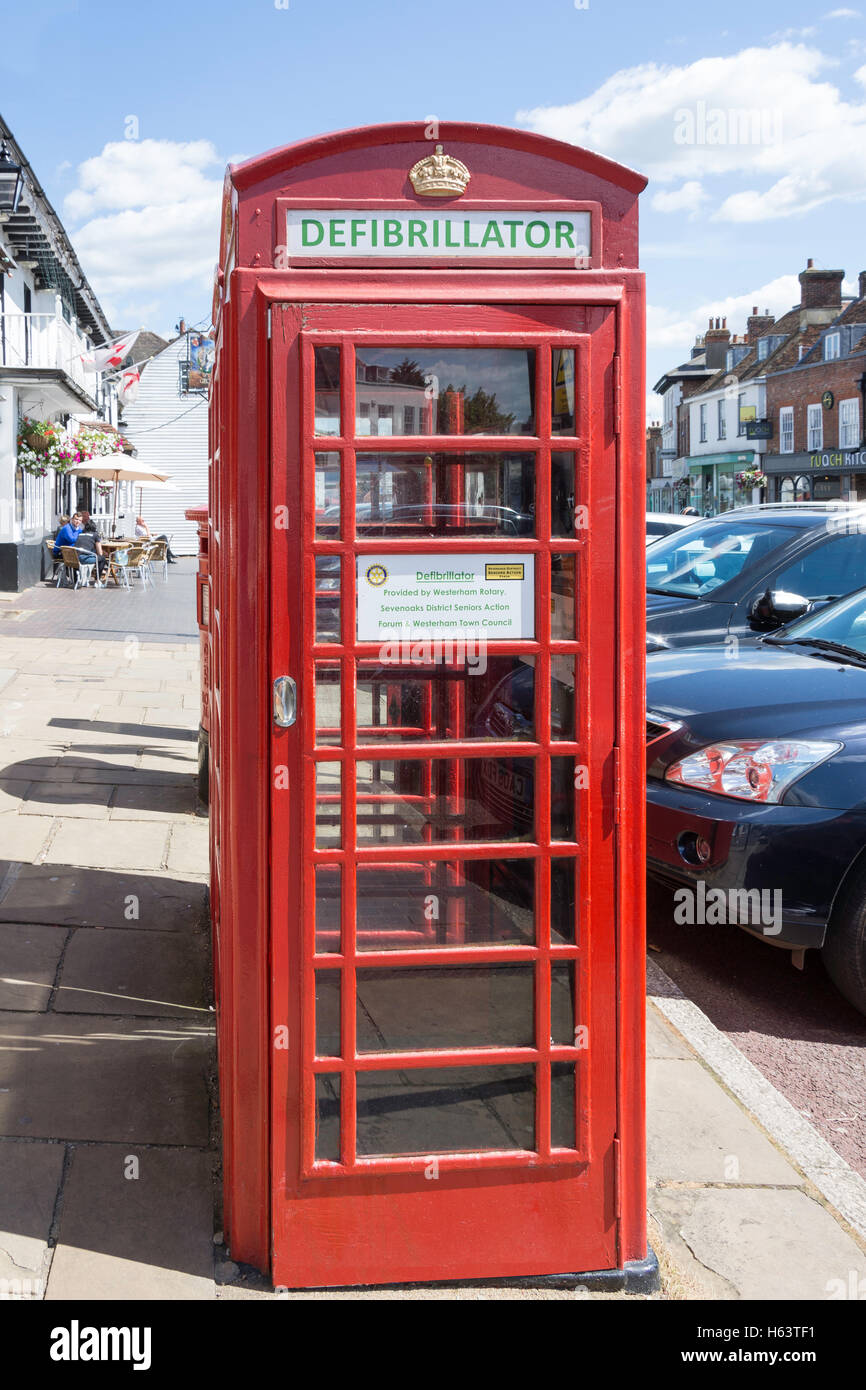 Red telephone kiosk with defibrillator inside, High Street, Westerham, Kent, England, United Kingdom - Stock Image