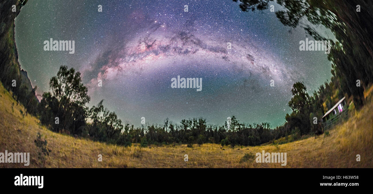 A 270° nightscape panorama of the Milky Way from Carina (at right) to Scutum (at left) arching over the paddock - Stock Image