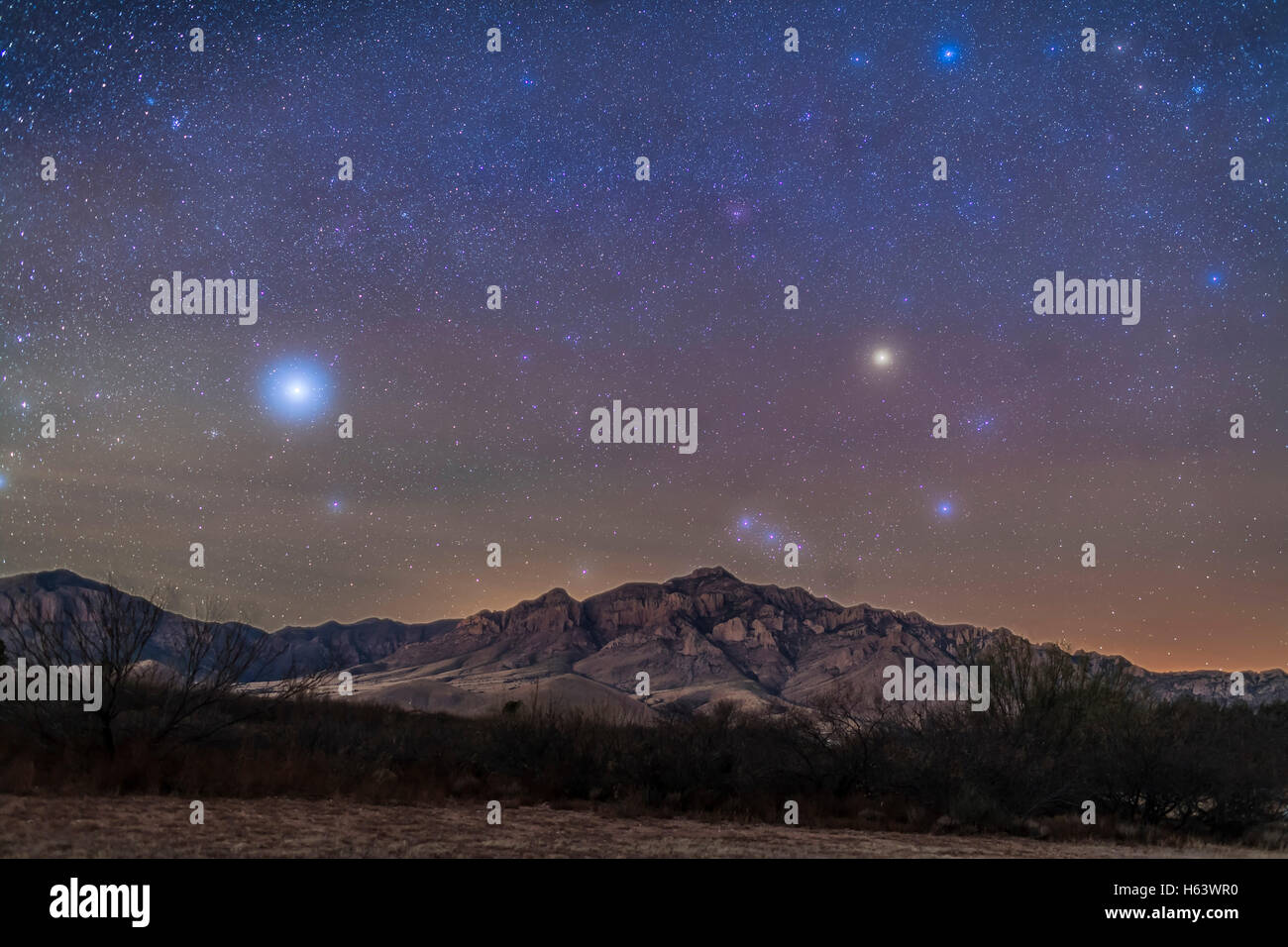 Orion and the star Sirius, at left, setting in the dawn sky over the Chiricahuas on the morning of December 9, 2015. Stock Photo