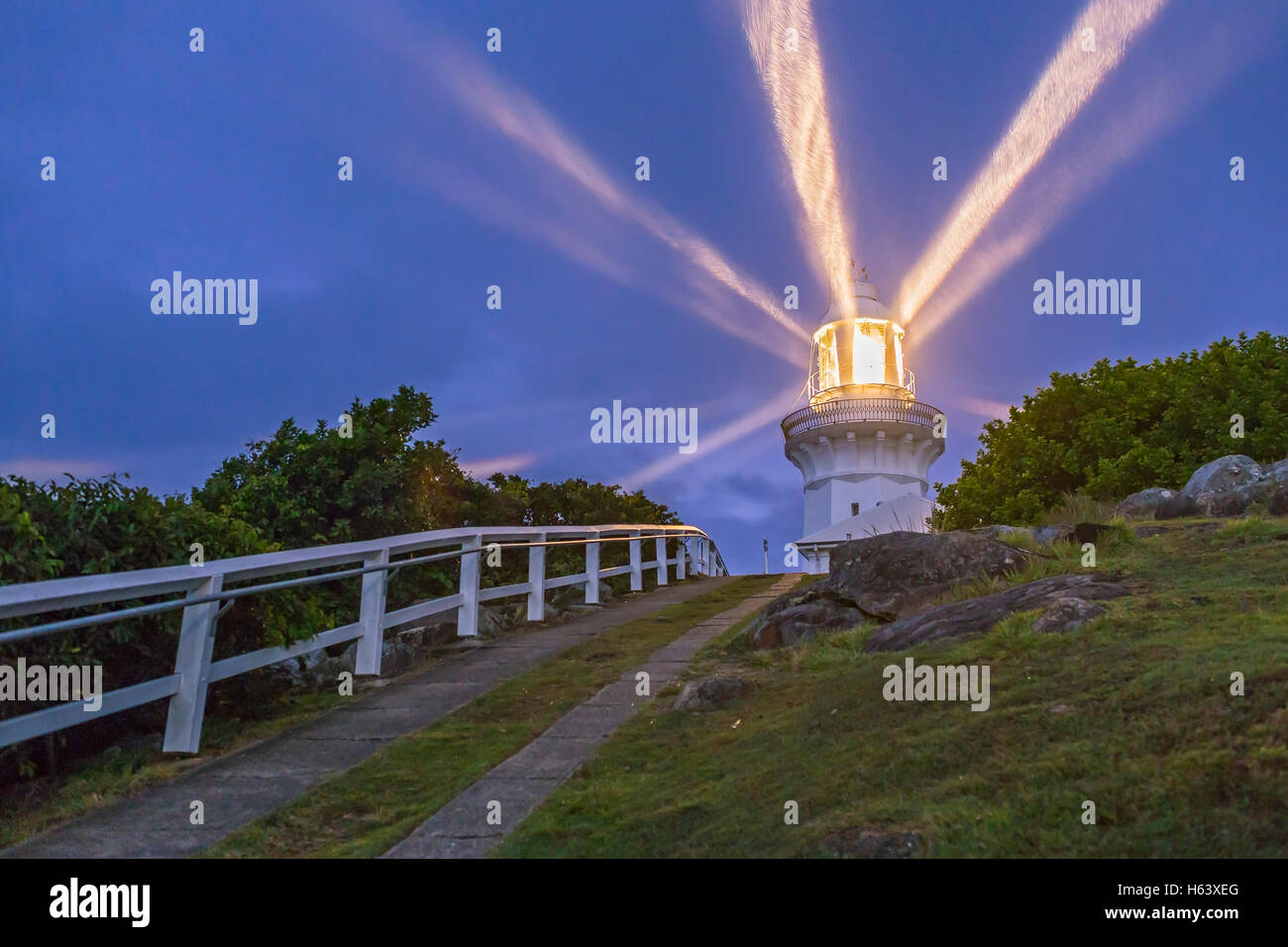 The Smoky Cape Lighthouse with its beams in the cloudy evening twilight shining in the light rainfall. This is near - Stock Image