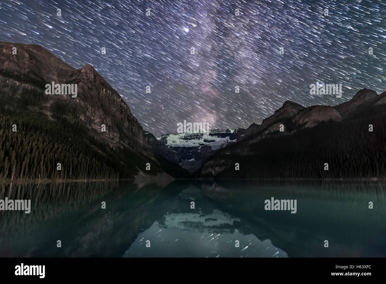 A composite of images stacked to create star trails descending over Lake Louise and Victoria Glacier in Banff National - Stock Image