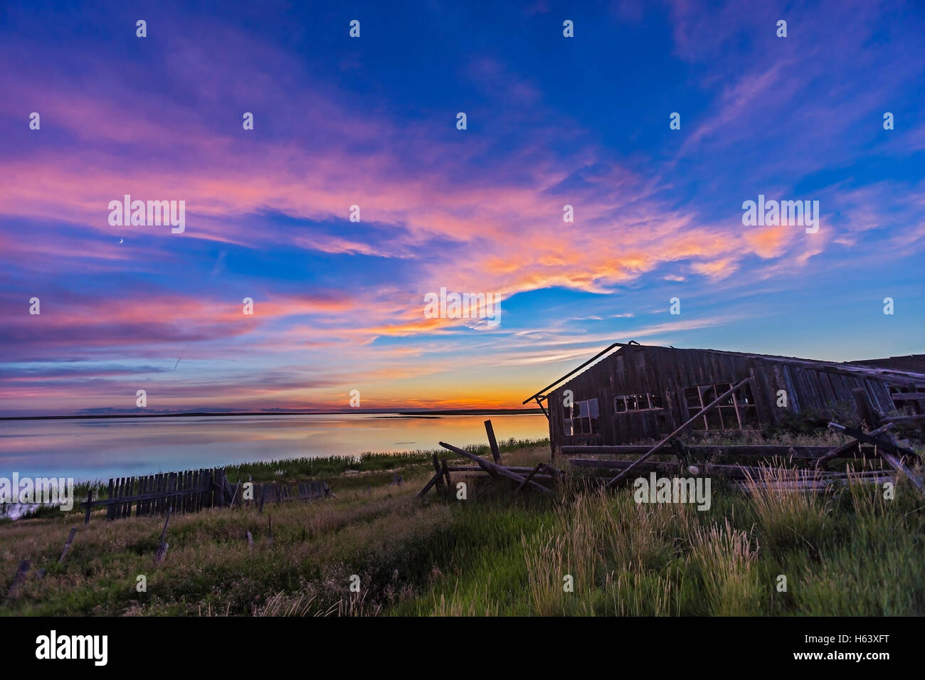 Sunset at Deadhorse Lake, in southern Alberta, with an abandoned farmstead building at the foreground element. The - Stock Image