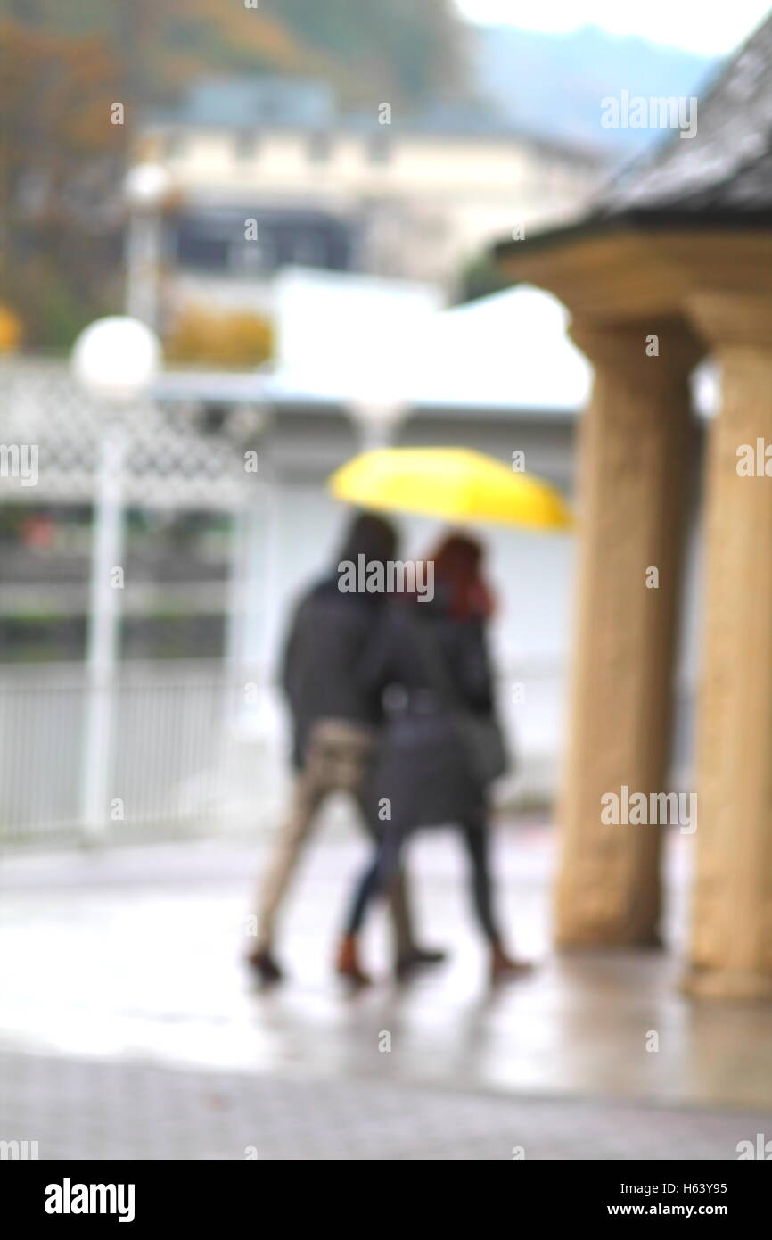 Blurred figures under yellow umbrella under fall rain. - Stock Image
