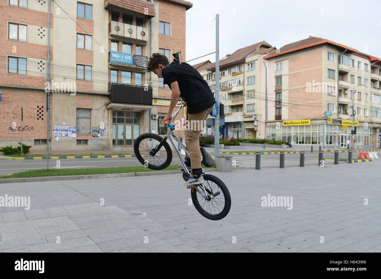 A young Romanian boy practicing stunts on his bicycle in the center of Suceava, Romania. - Stock Image