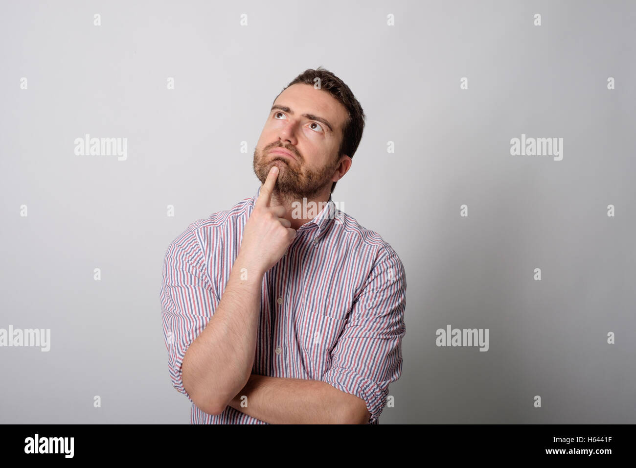 Resigned man on gray background - Stock Image