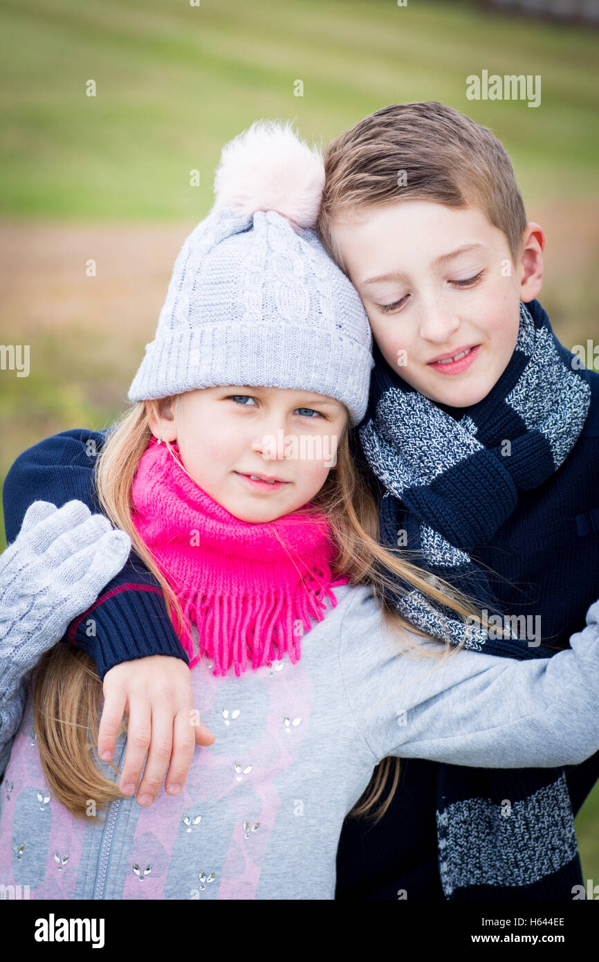 Brother and sister posing outdoors in autumn wearing worm clothes and feeling happy together - Stock Image