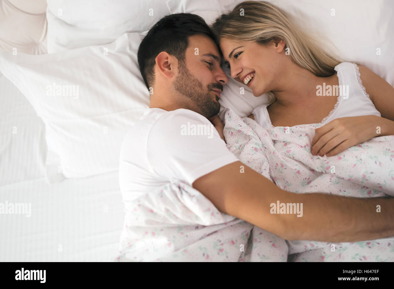 Romantic couple in bed in nightwear smiling Stock Photo