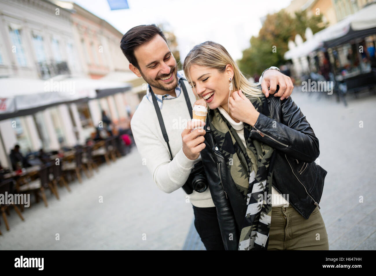 Tourist couple sharing ice cream outdoors and smiling - Stock Image